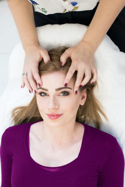 Jowita Trzaska przykłada dłonie do głowy swojej klientki-młodej kobiety- w trakcie sesji energetycznej access bars
