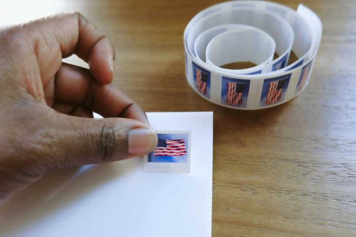 Woman Places Postage Stamp on Envelope