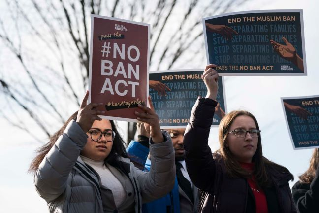 People hold signs showing their support of ending a travel ban on Muslim-majority countries at a news conference outside of the US Capitol last month. Senate and House Democrats are calling for the passage of the NO BAN Act to end President Trump's travel bans, which they call discriminatory.