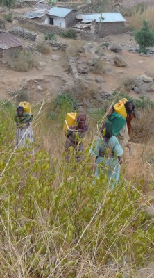 Women carrying 25litre drums of irrigation water up an eroded hillside