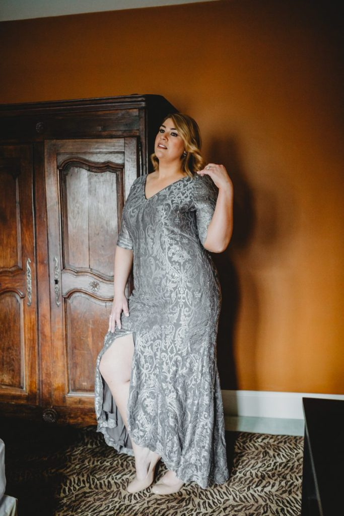 A beautiful plus size woman in a formal gown of gray brocade
