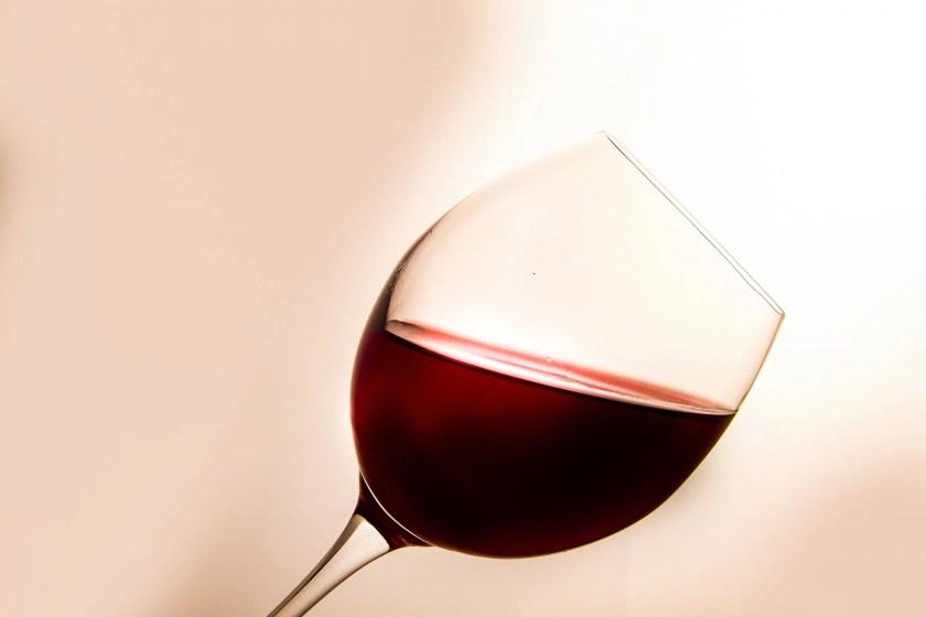 Ein schräg nach rechts geneigtes Weinglas, das mit Rotwein gefüllt ist.