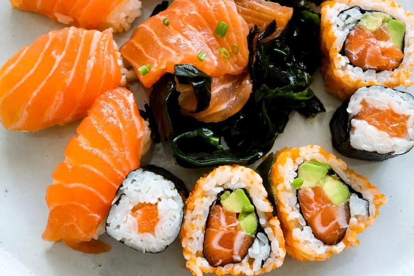 Lachs-Sushi als Nigiri, Maki, Sashimi und California Roll.