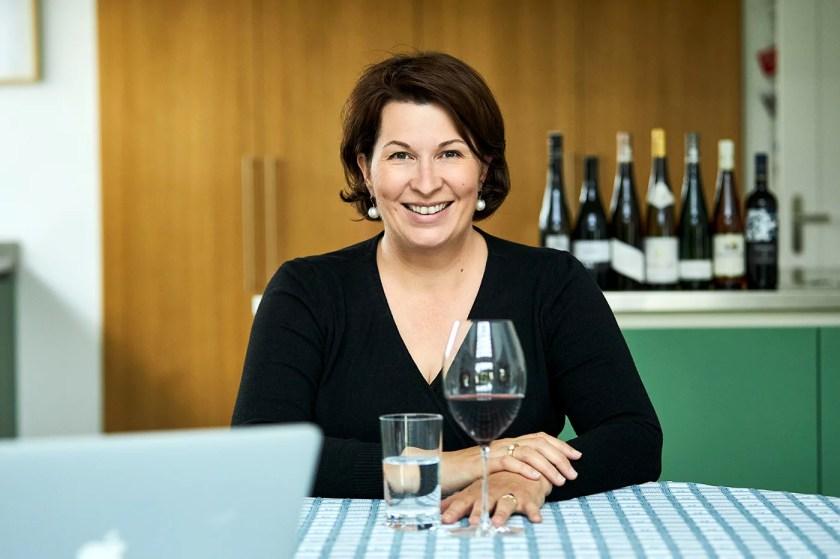 Romana Echensperger an einem Tisch vor sich ein Glas mit Wasser und ein mit Rotwein gefülltes Weinglas.