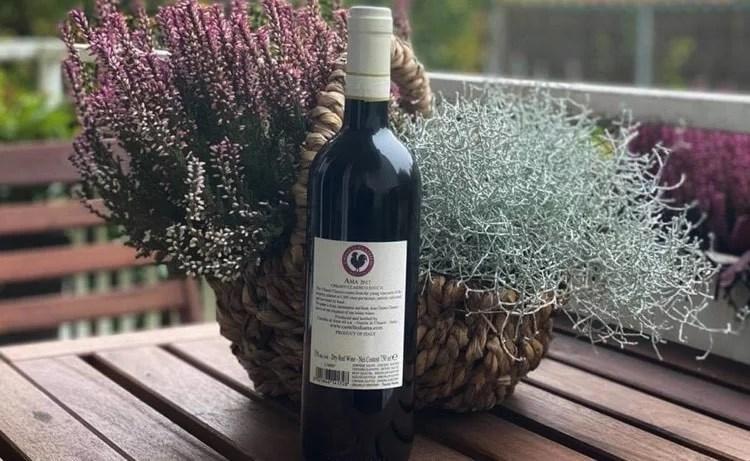 Flasche Chianti Classico mit dem Gallo Nero auf der Rückseite auf einem Tisch vor einem Korb mit Heide