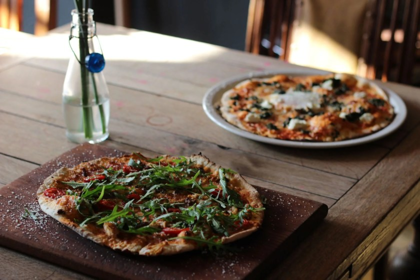 Welcher Wein zu Pizza: Zwei Pizzen auf einem Holztisch.