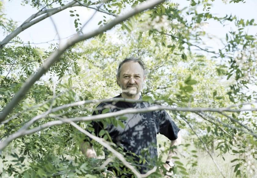 Winzer Hans Nittnaus durch die Zweige eines Baums hindurch fotografiert.