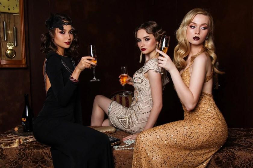 Drei edel gekleidete Frauen stoßen mit Champagner an.