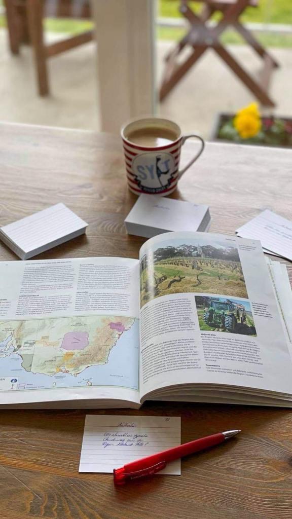 Aufgeschlagenes Buch, Lernkarten und ein Kaffee auf einem Tisch