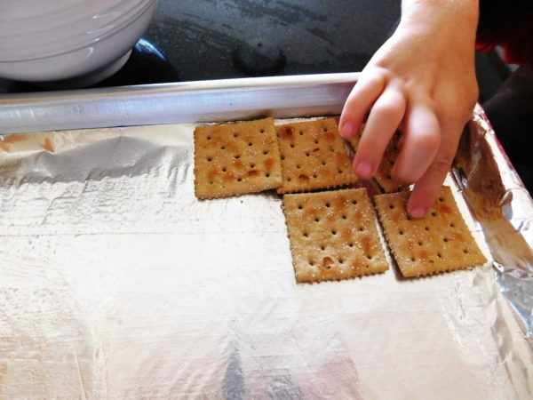 A little hand laying out crackers on a sheet pan.