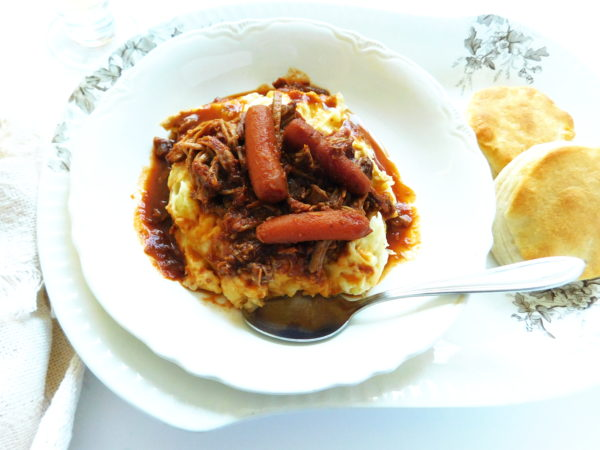 Beef Ragu and tomato gravy over mashed potatoes with rolls on the side ready to eat.