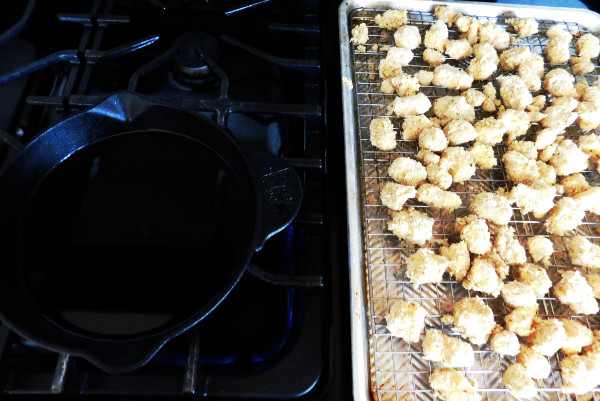Cheese curds on a pan and a pan on the stove with oil in it ready to fry the cheese curds.