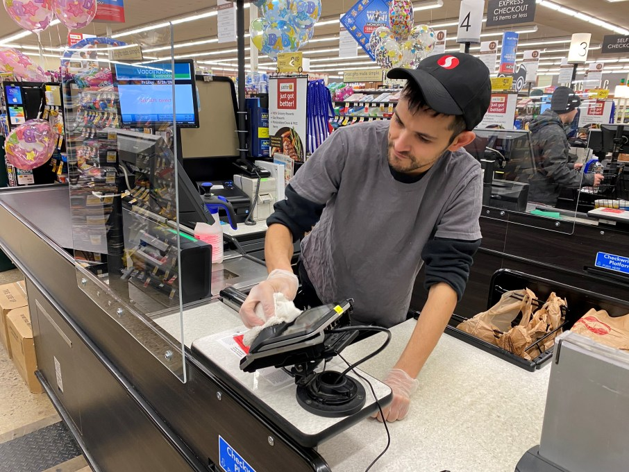 Safeway employee cleaning checkstand