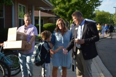 John Suitor, author and Head of School, greeting student and mother on the sidewalk.