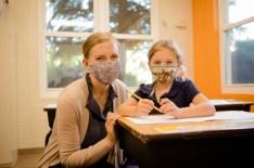 Female teacher and student at desk both wearing masks.