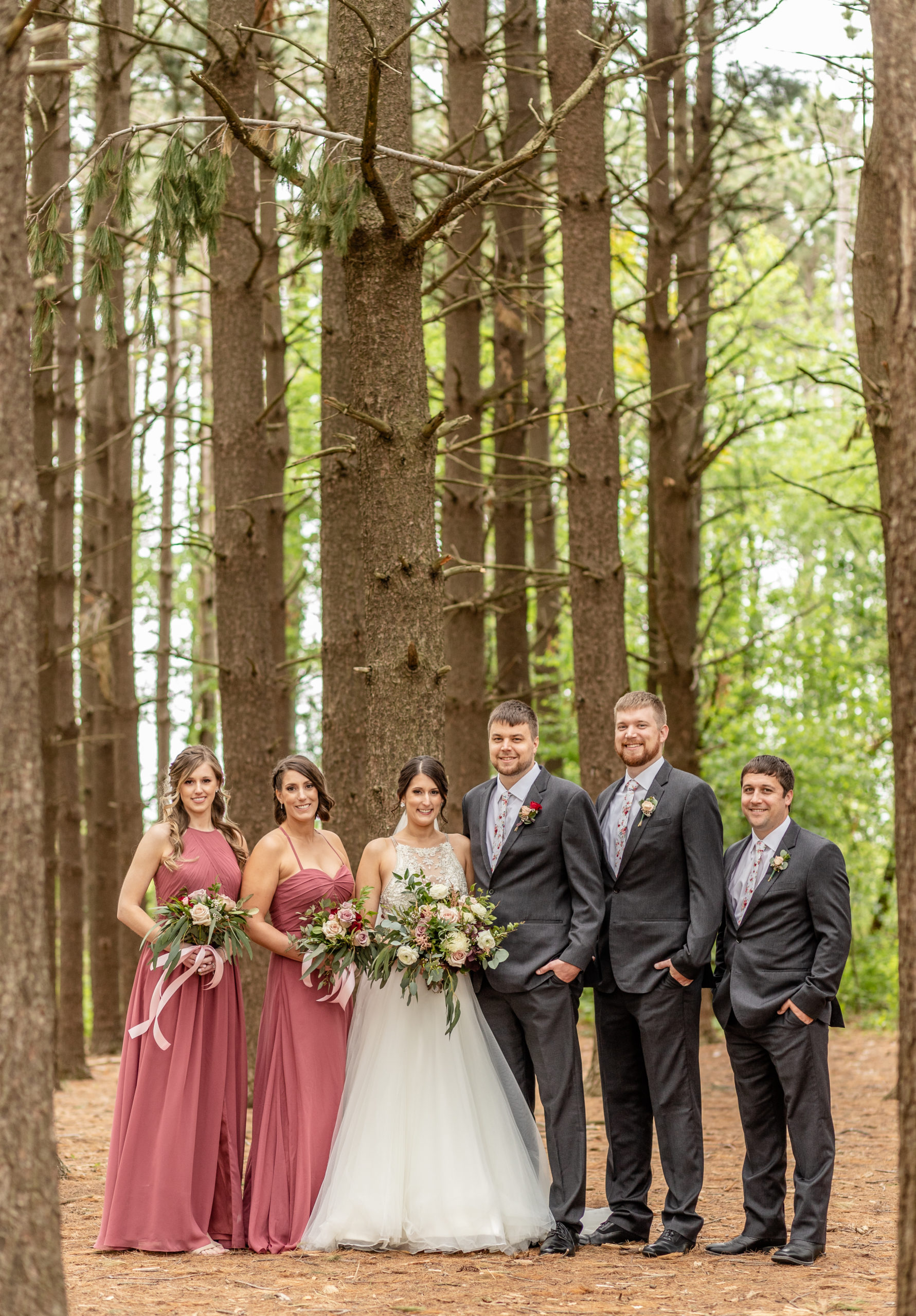 wedding party, pine trees, grey suit, wedding dress, bouquets, rusty pink