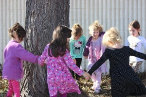 JCC Preschool class dances around the tree outside the Boulder JCC