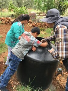 Arava Institute intern, Dominik Wendschlag, shows local children how to test the water quality of one of the greywater systems.