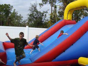 backyard slide water event birthday party rental orange city blue red yellow