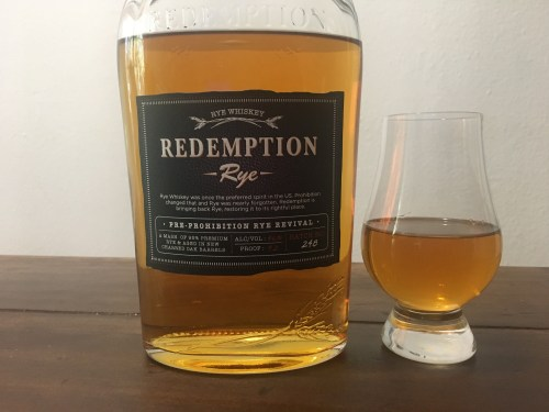 Bottle of Redemption Rye with glencairn glass on table.