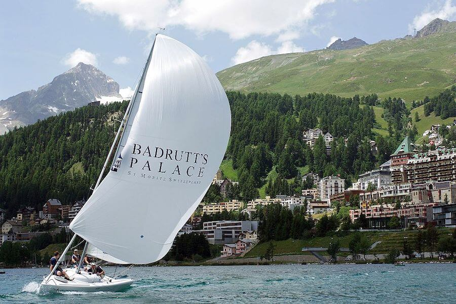 Badrutt's Palace's sailing boat. with white sails bellowing, as it races along Lake St Mortiz with a backdrop of pine clad mountains, Switzerland