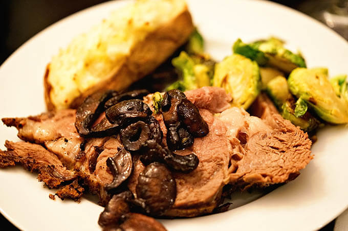 A white plate serving up Prime Rib Dinner with steak topped with mushrooms, twice baked potatoes and Brussels sprouts