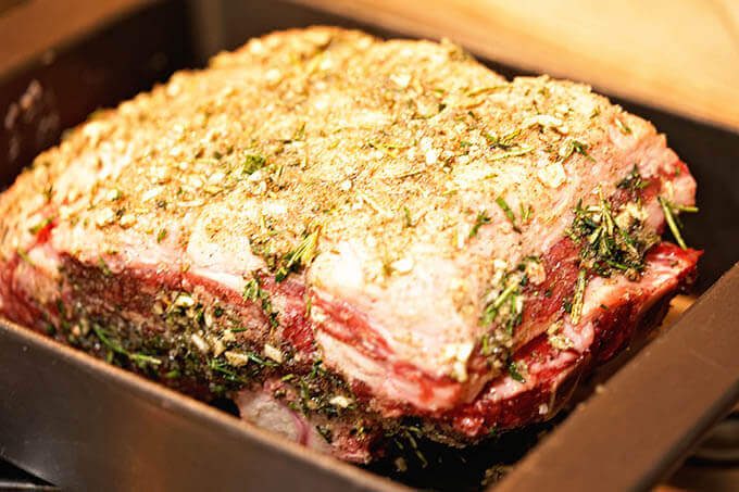 A prime rib roast seasoned with a garlic and herb rub.