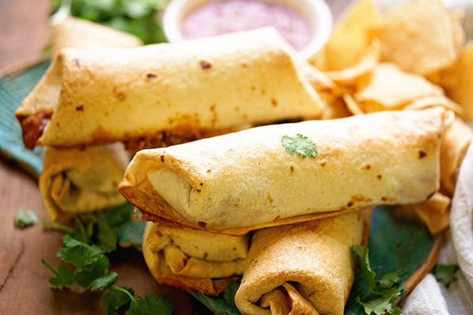 A platter of crispy chimichangas piled on a platter.