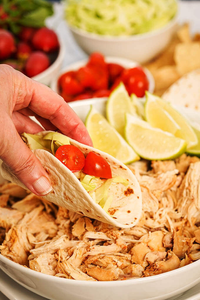 A white bowl filled Slow Cooker Chicken Taco meat with
