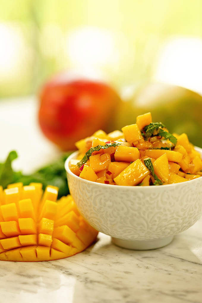 Easy Mango salsa recipe in a white bowl surrounded by fresh sliced mango and mint.