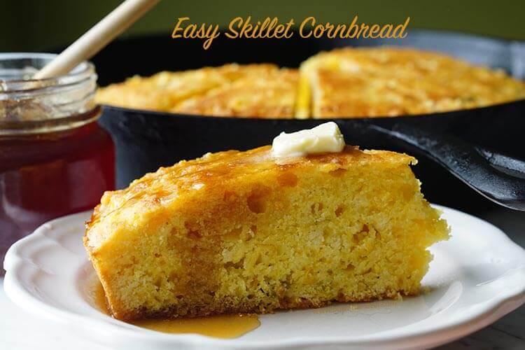 Cast Iron Skillet Cornbread Recipe on a white plate topped with butter and honey.