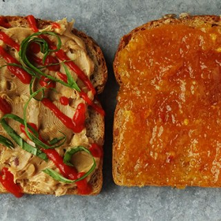 Two slices of bread, one spread with peanut butter and drizzled with hot sauce, the other slice is spread with orange marmalade.