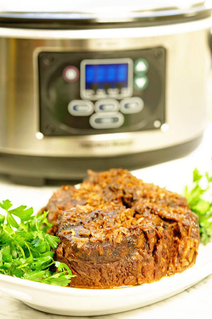 Easy Slow Cooker Roast Beef Recipe - plated on a white platter with green parsley