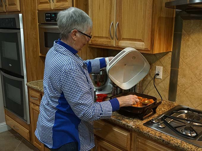 Woman basting sweet potatoes in pan with syrup
