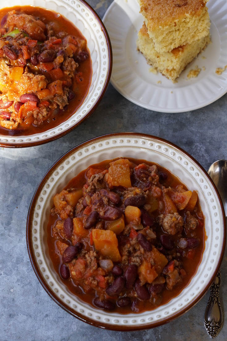 Two bowls of chili with a couple servings of cornbread on the side.