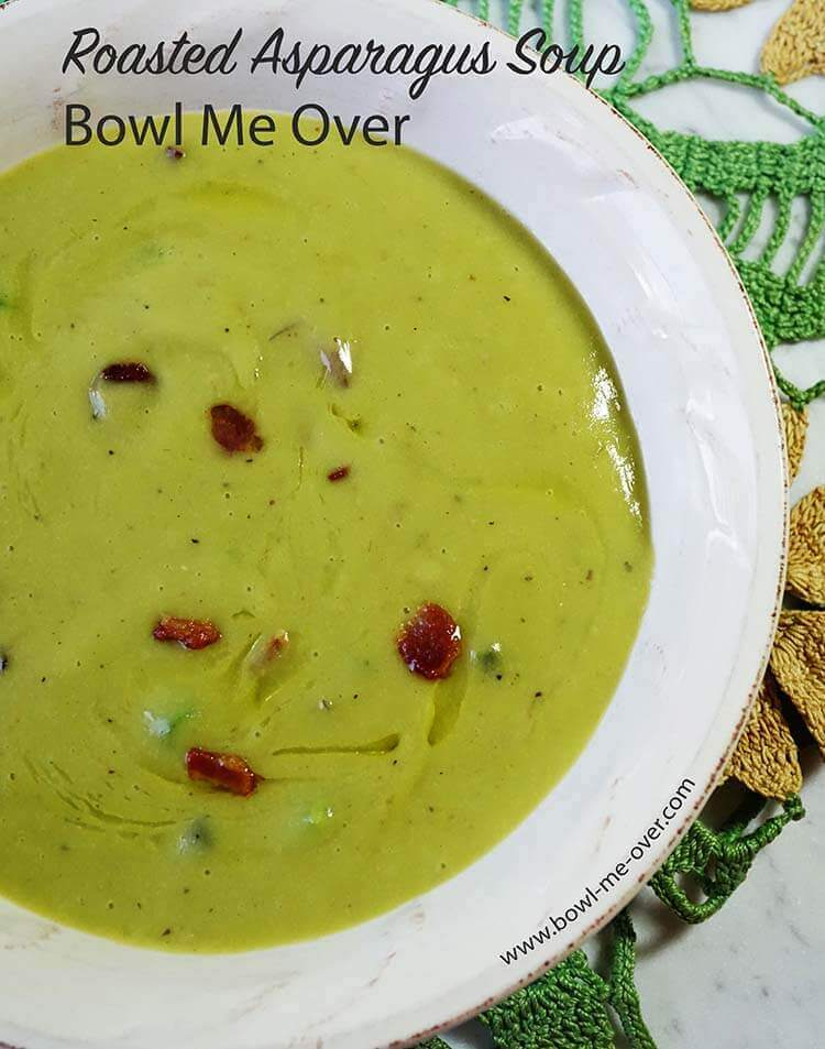 A bowl full of bright green asparagus soup! The soup is topped with crunchy bacon bits