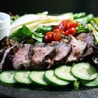 Grilled pork tenderloin salad with vegetables on silver platter.