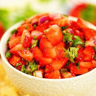Strawberry salsa in a white bowl surrounded by chips and fresh strawberries