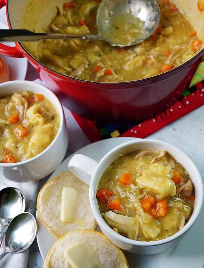 White mugs filled with an easy Chicken and Dumpling Soup Recipe. There are butter biscuits to serve with your meal and a red stockpot with a ladle so you can scoop out seconds!