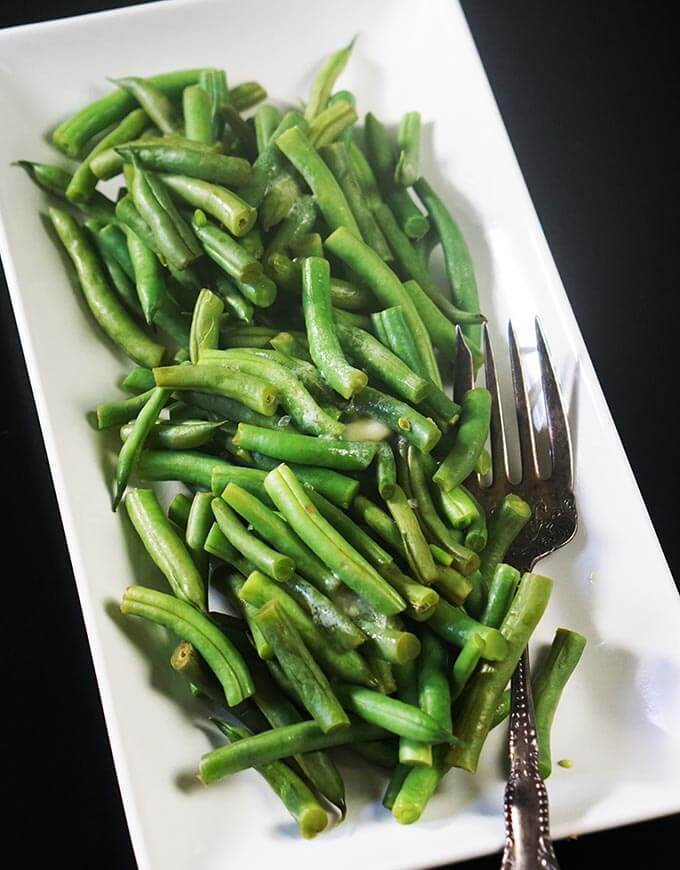 Steamed Green beans on a white platter sitting on a black tablecloth.