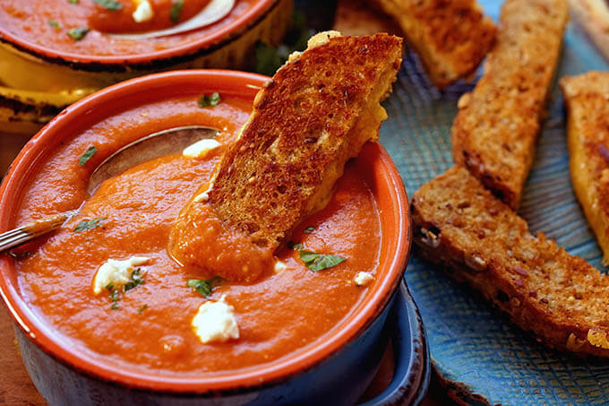 A toasted cheese sandwich being dunked into a bowl Tomato Soup.