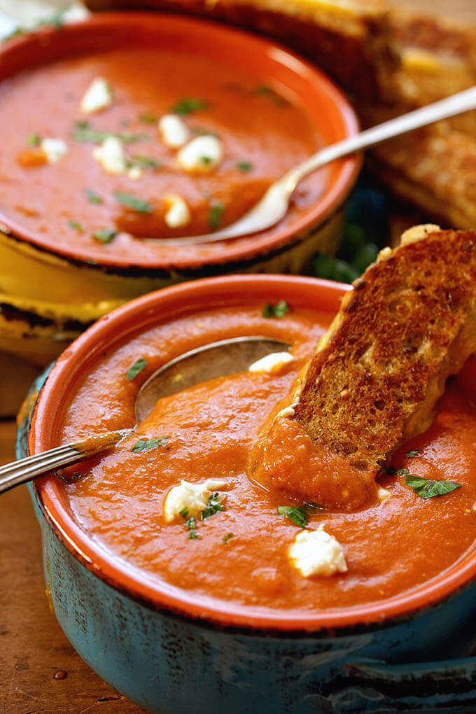 Two bowls of tomato bisque soup topped with goat cheese and served with grilled cheese sandwich.