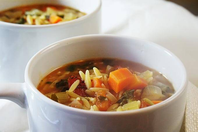 Two white bowls fill with vegetable orzo soup sitting on a white table cloth.