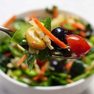 White bowl filled with kale superfood salad recipe with fork.