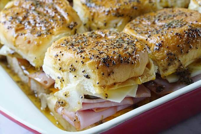 Cuban sliders in baking dish topped with sesame seeds.