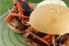 Pulled Pork Sliders on green plate topped with coleslaw