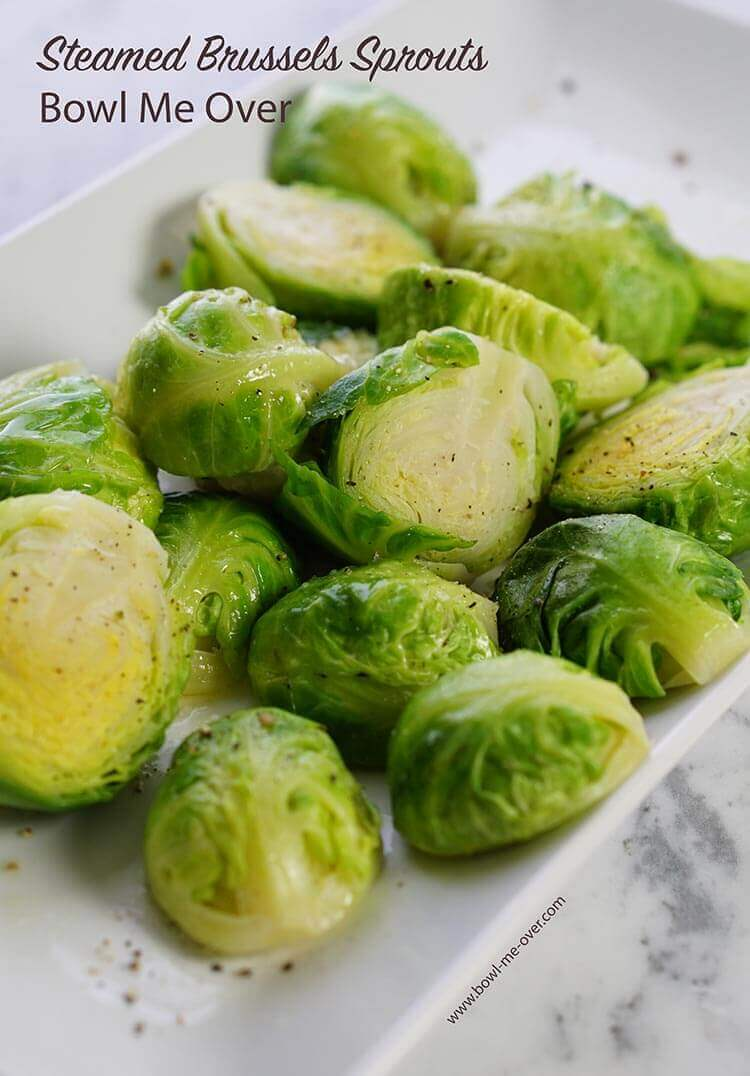 A white plate on a marble countertop. The plate is full of steamed fresh Brussels sprouts!