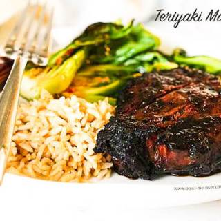 Best Teriyaki Marinaded Steak with recipe and greens on white plate.