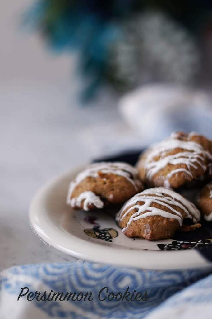 Persimmons Cookies drizzled with white chocolate on white plate.