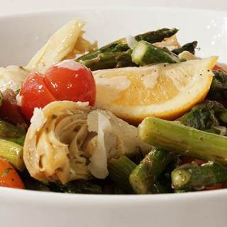 A white bowl filled with wedges of lemon, sliced tomatoes, marinated artichoke hearts and roasted asparagus.